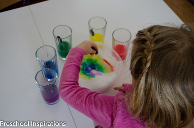 a preschool girl making a colorful rainbow in snow with liquid watercolors