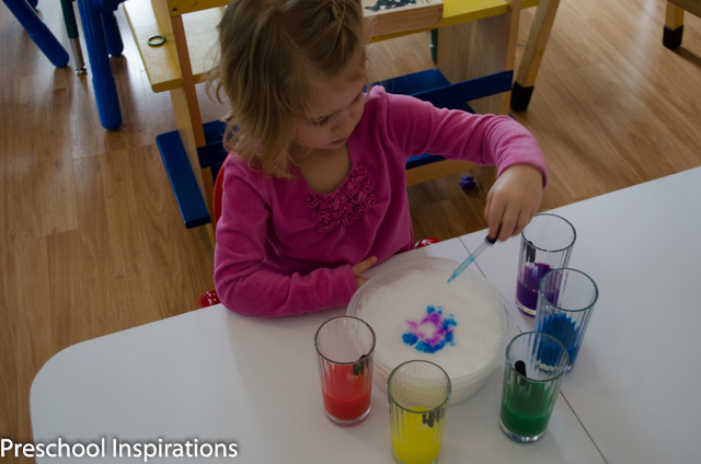 a preschool girl paining on snow with liquid watercolors