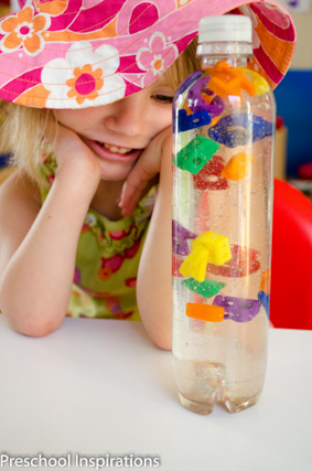 A young girl in a flowered hat smiling at an alphabet discovery bottle