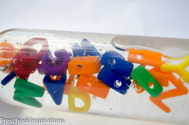 A clear bottle filled with alphabet lacing letters turned on its side