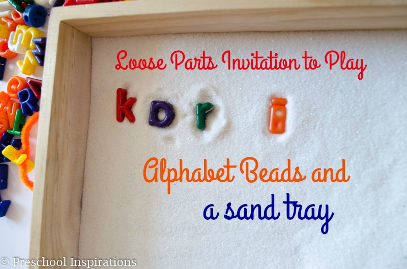 Loose parts invitation to play Alphabet Beads and a Sand tray