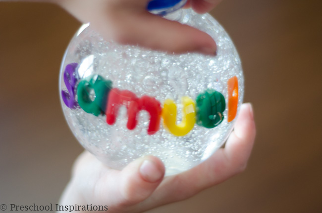 a boy's hands holding a name sensory bottle that spells samuel
