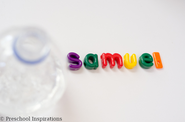 colorful alphabet beads spelling the name 'samuel' next to a plastic water bottle with hair gel