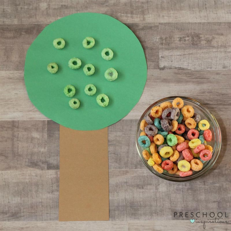 green fruit loops placed on a tree made of construction paper made to look like apples