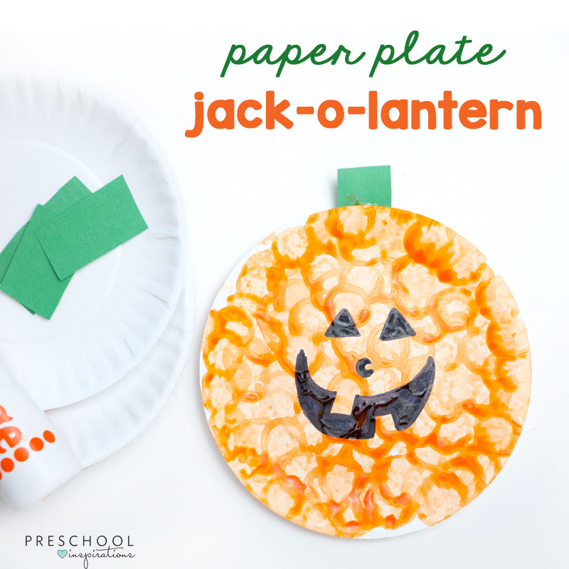 a jack-o-lantern made out of a paper plate, construction paper, and a dauber marker