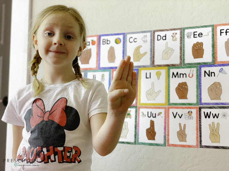 young girl proudly holding up the letter B in ASL