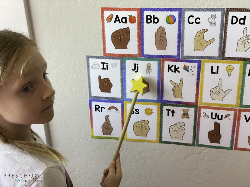 a young girl using a pointer with ASL alphabet wall cards