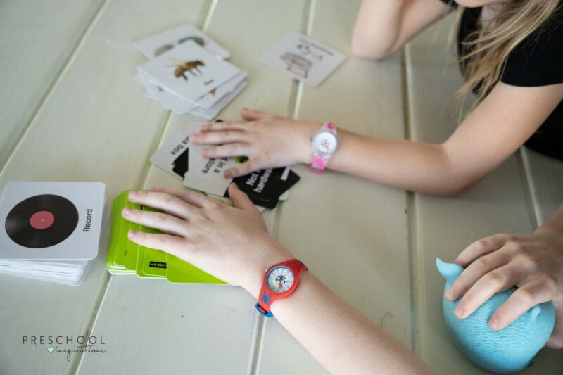 two hands wearing time-teaching watches playing a card game