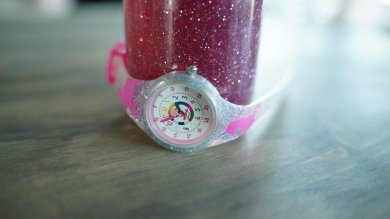 a unicorn time telling watch wrapped around a glitter sensory jar