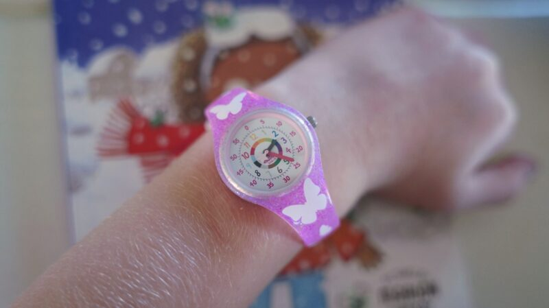 a watch designed to teach time with a butterfly band on a young girls' wrist