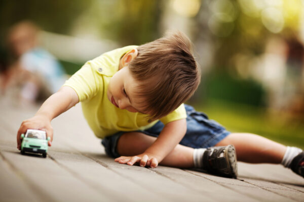 little boy of potty-training age plays outside with toy car