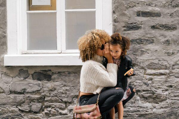 mother whispers secrets into her preschool daughter's ear