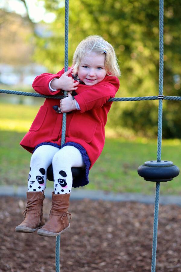 a confident preschooler in a red coat hangs smiling from a climbing net