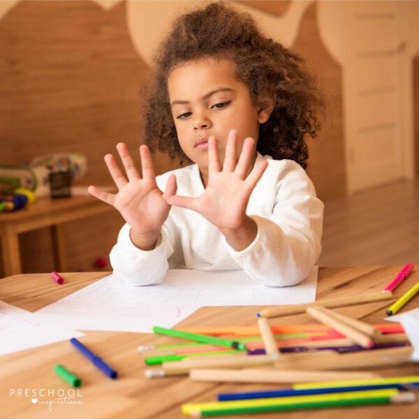girl holds up all 10 fingers