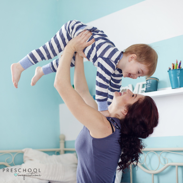 a mother throws her smiling little boy in the air