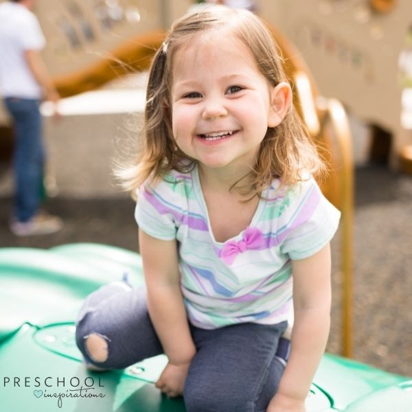 a grinning toddler plays on the playground