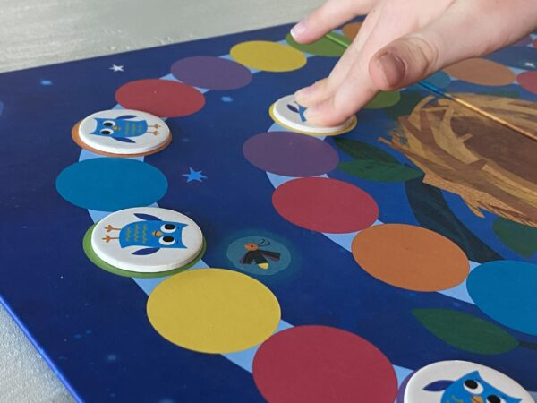 a child's hand playing the board game hoot owl hoot