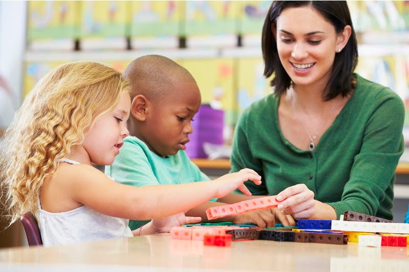 image of a child counting snap cubes with a teacher