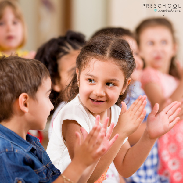 two preschoolers smile and clap during a preschool circle time